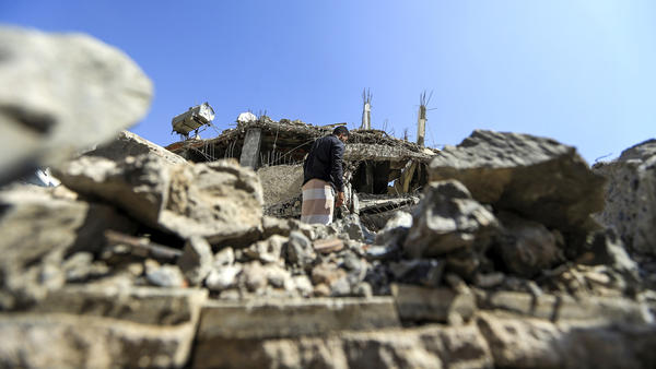 "A Yemeni man walks through the rubble of a building after a Saudi-led coalition airstrike last month in the capital, Sanaa. ""The time is now for the cessation of hostilities,"" U.S. Secretary of State Mike Pompeo said Tuesday."