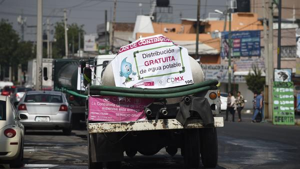 A tank truck distributes free water to homes and other nonprofit locations while service is cut off for maintenance in Mexico City.