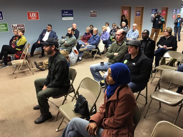 Ilhan Omar (lower right) sits with a crowd of volunteers and Democratic Farmer Labor party members.