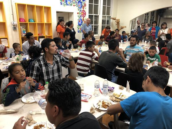 Families eat dinner at Holy Family Church in El Paso. Immigration officials have been releasing hundreds of asylum-seeking migrants into border communities. Churches and shelters are standing by to help.