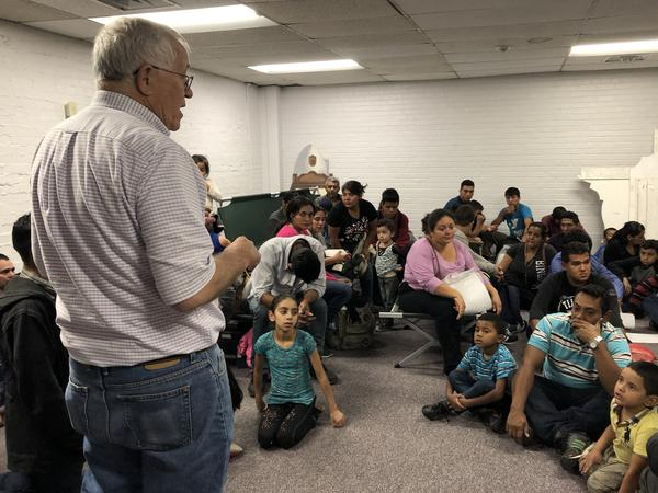 Annunciation House director Ruben Garcia welcomes migrant families to Holy Family Church, which agreed to take them in for the night after they were dropped off at a Greyhound Station.