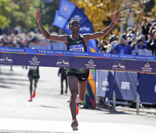 Lelisa Desisa, of Ethiopia, crosses the finish line first in the men's division of the NYC Marathon.