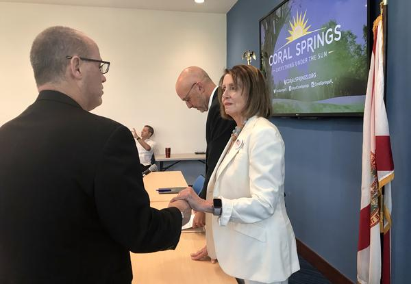 Democratic Leader Nancy Pelosi, right, greets Parkland father Fred Guttenberg, left, Wednesday in Coral Springs City Hall. U.S. Rep. Ted Deutch, center, hosted a roundtable to talk about gun violence prevention.