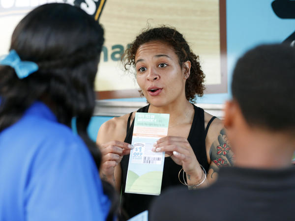 """Jessica Jones (center) speaks to people gathered around the Ben & Jerry's """"Yes on 4"""" Truck about Florida's Amendment 4 initiative at Charles Hadley Park in Miami, on Oct. 22. Amendment 4 asked voters to restore the voting rights of people with past felony convictions."""
