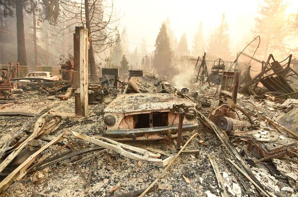 The charred remains of a vehicle and home in Paradise destroyed by the Camp Fire on Thursday.