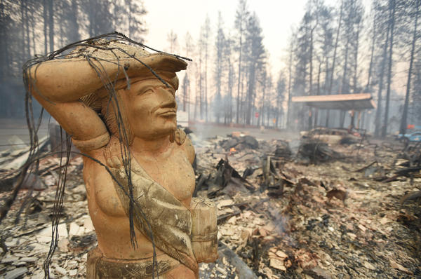 A statue stands amid the rubble of a smoldering property Thursday in Paradise, which was ravaged by the Camp Fire.