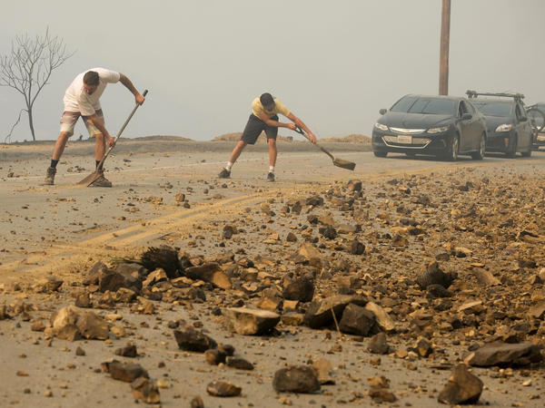 Malibu residents clean up the road after the destruction of the Woolsey Fire on Saturday.