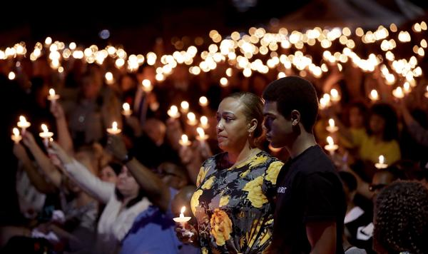 Veronica Hartfield stands with her son Ayzayah Hartfield during a candlelight vigil for her husband, Las Vegas police officer Charleston Hartfield, Thursday, Oct. 5, 2017, in Las Vegas. Hartfield was killed during the shooting at the Route 91 Harvest country music festival.