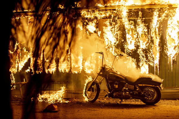 A structure and a motorcycle burn at an RV park during the Woolsey Fire in Malibu.