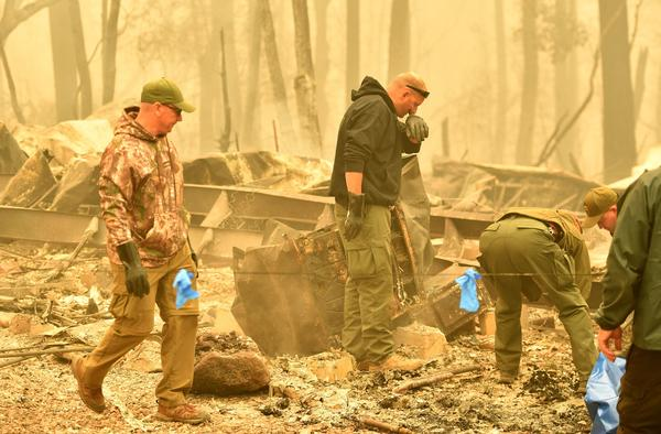 Officers react as they discover a body at a burned residence after the Camp Fire tore through the area in Paradise.