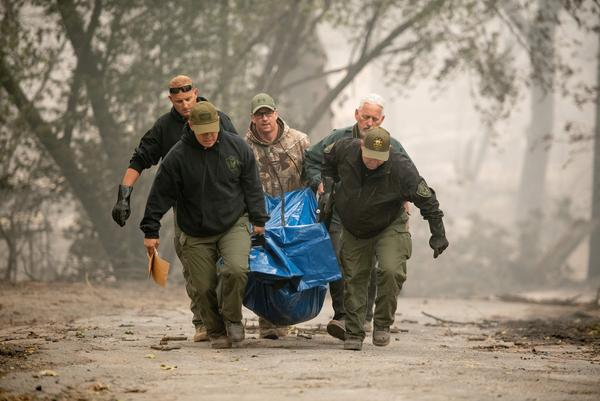 Yuba County Sheriff's Office officials carry a body away from a burned residence in Paradise.