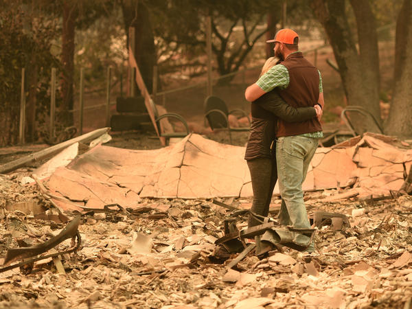 Chris and Nancy Brown embrace Monday while looking over the remains of their burned residence after the Camp Fire tore through the region in Paradise, Calif. Dozens of people have been killed in the latest fires to hit the state.
