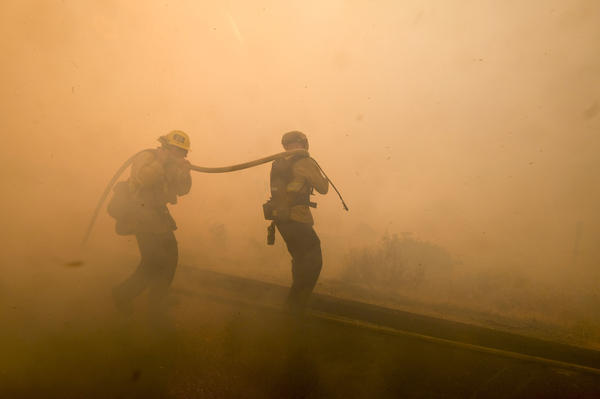 Firefighters battle a fire along the Ronald Reagan Freeway in Simi Valley, Calif.
