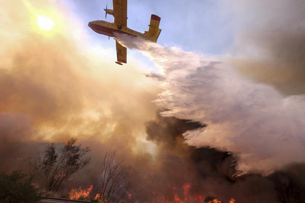 An air tanker drops water on a fire along the Ronald Reagan Freeway in Simi Valley, Calif.