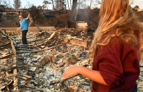 Matty Winters, 13, watches her father Shannon pick up what's left of a book at the Seminole Springs mobile home park in Malibu Lake after the Woolsey Fire roared through the community.