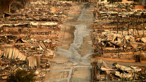 A man stands in the middle of the street at the Seminole Springs mobile home park in Malibu Lake after the Woolsey Fire roared through the community.