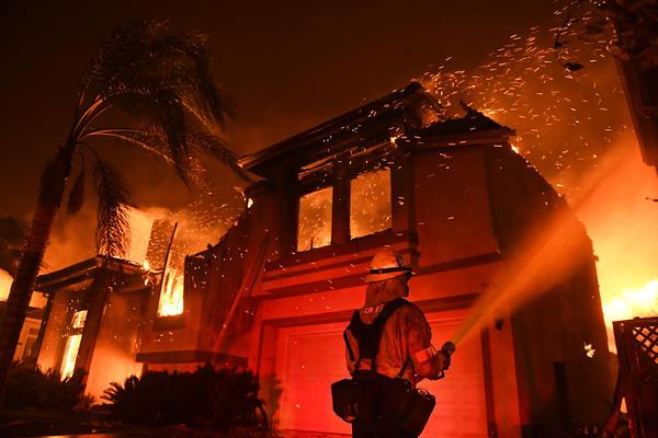 A firefighter battles a house fire in the Oak Park neighborhood.