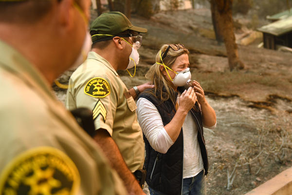 Anne Marie Mueller is consoled by L.A. County sheriff's officer Ernie Ferreras after he notified her that her friends were safe from the Woolsey Fire in Malibu.