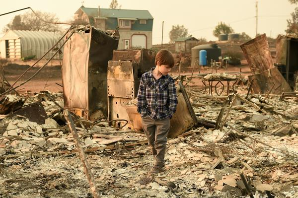 Jacob Saylors, 11, walks through the burned remains of his home in Paradise, Calif., Sunday. His family lost a home in the same spot to a fire 10 years earlier.