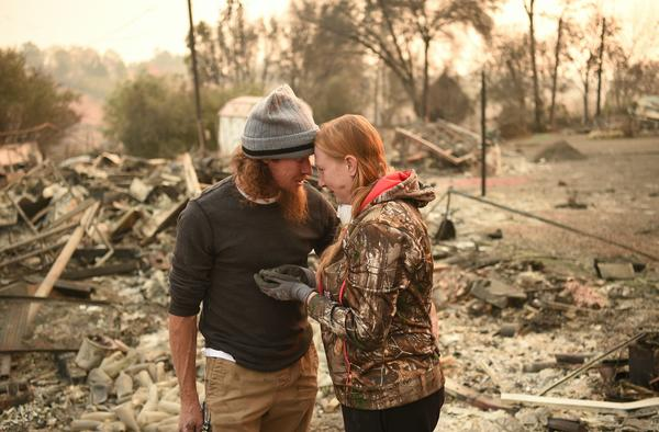 Ryan Spainhower and his wife Kimberly discover a coin they had made during their honeymoon amidst the burned ashes of their home in Paradise, Calif., on Sunday.