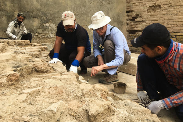 American conservationist Jeff Allen (center) directs Iraqi technicians laying mortar between ancient bricks at the site of Babylon.