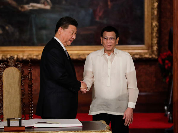 "Chinese President Xi Jinping (left) shakes hands with Philippine President Rodrigo Duterte after a guest book signing at the Malacañang presidential palace in Manila on Tuesday. Duterte called Xi's visit to longtime U.S. ally the Philippines a ""milestone."""