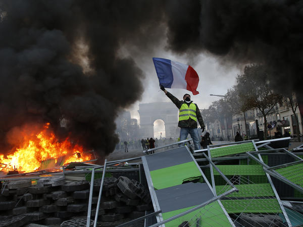 "A protester holds a French flag above Paris' Champs-Elysees avenue on Saturday. Many demonstrators believe that French President Emmanuel Macron is far removed from the problems of the ""little people."""