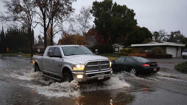 Vehicles pass each other on a flooded street in Chico, Calif. Flash flooding hit a wildfire-scarred area of Northern California on Thursday, forcing officials to deploy swift water rescue teams to save people stuck in vehicles and rescue them from homes after a downpour near the Paradise area.