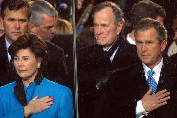 Bush attends the inaugural parade for his son, President George W. Bush, in January 2001. His daughter-in-law first lady Laura Bush is at left.