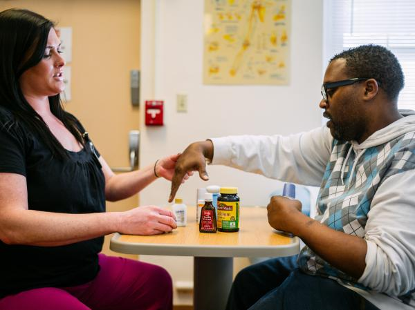 "Occupational therapist Lydia Bongiorni works with Troy Hodge on grasping and lifting objects at a rehabilitation center in Gwynn Oak, Md. ""You basically have to start over again,"" Hodge says. ""You retrain your brain to use your limbs."""