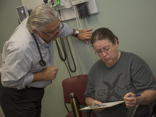Dr. Ronald Cirillo helps Deborah Hatfield fill out paperwork at a Florida clinic, before running a test to see whether she has hepatitis C.