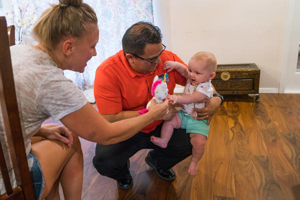 Carlos Garcia plays with six-month-old Evin Wilson, with Evin's mother, Jacqui Wilson.