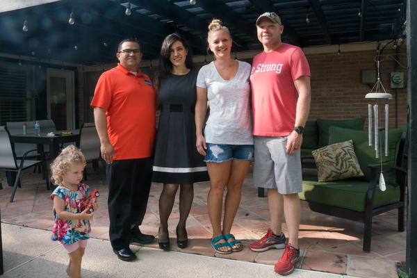 Carlos and Elizabeth Garcia (left) with Ben and Jacqui Wilson, at the Garcia's home in McAllen, Texas. The Wilson's daughter, Colby, 2, walks in the front.