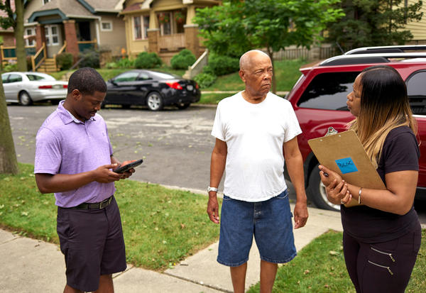 Wisconsin State Rep. David Crowley, left, works with Keisha Robinson, right, of BLOC, Black Leaders Organizing for Communities as he takes part in a silent canvass where Mr. Crowley is only allowed to listen to community members like George McBeth, center, Aug. 8, 2018 Milwaukee.