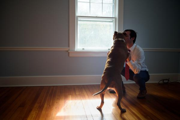 Burke with his emotional support dog, Rosie, in his home in Weston, Conn.