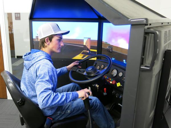 Watford City High School senior Jake Lepell practices driving on the school district's $20,000 truck driving simulator. The region's oil boom has created a demand for truck drivers.