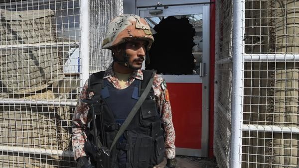 A Pakistani ranger stands in front of a damaged gate at the Chinese consulate after an attack in Karachi on Friday.