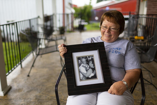 """Lisa Hobbs holds a picture of her husband, Gene """"Pius"""" Hobbs. Hobbs was raking gravel with the Meade County public works crew when a dump truck backed over and killed him."""