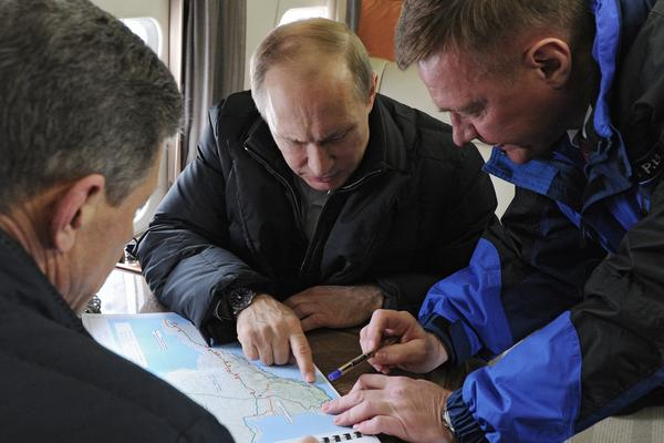 Russian President Vladimir Putin (center), aboard a helicopter, points at a map while inspecting the site for a bridge across the Kerch Strait in March 2016. Today, the bridge links Russia and the Crimean Peninsula.