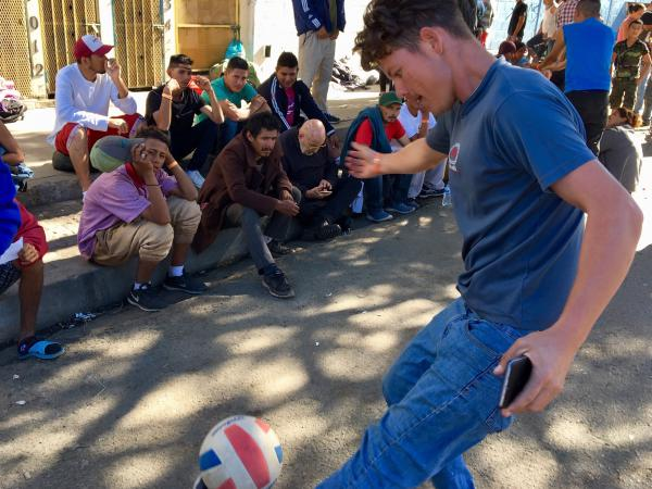 Street soccer - and watching it - passes the long days of waiting for migrants.