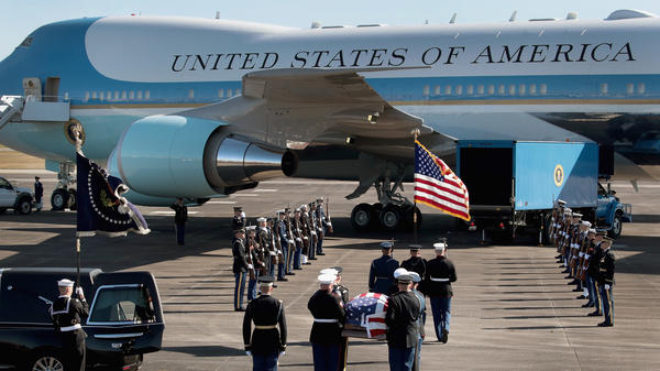 The remains of former President George H.W. Bush are carried to Special Air Mission 41 by a military honor guard before flying to Washington, D. C., Monday in Houston, Texas.