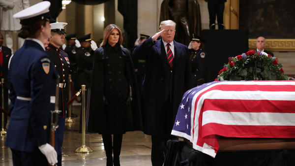 President Trump salutes as he and first lady Melania Trump pay their respects as former President George H.W. Bush lies in state in the U.S. Capitol Rotunda Monday in Washington, D.C.