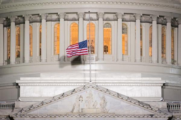 An American flag flies at half staff in front of the U.S. Capitol building.