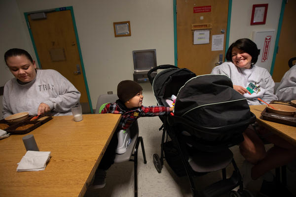 Kirshawn, 2, makes a new friend  with a newborn in a stroller next to him during the inmates' breakfast meal.