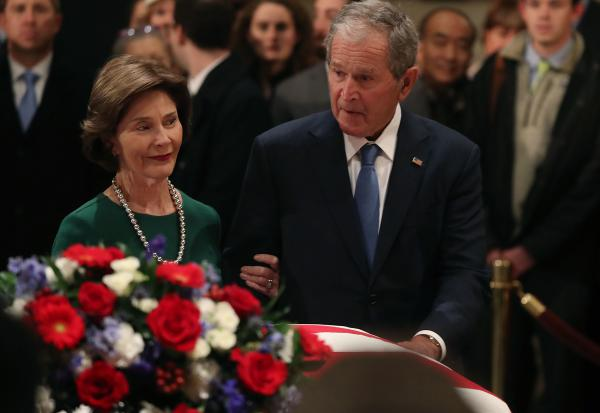 Former U.S. President George W. Bush and his wife Laura Bush pay their respects in front of the casket of the late former President George H.W. Bush as he lies in state in the U.S. Capitol Rotunda, Tuesday in Washington, D.C.