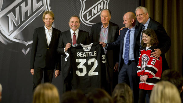 NHL commissioner Gary Bettman (center left) presents a jersey with No. 32, signifying that Seattle is soon to be the NHL's 32nd active franchise. The NHL Board of Governors announced the expansion Tuesday.