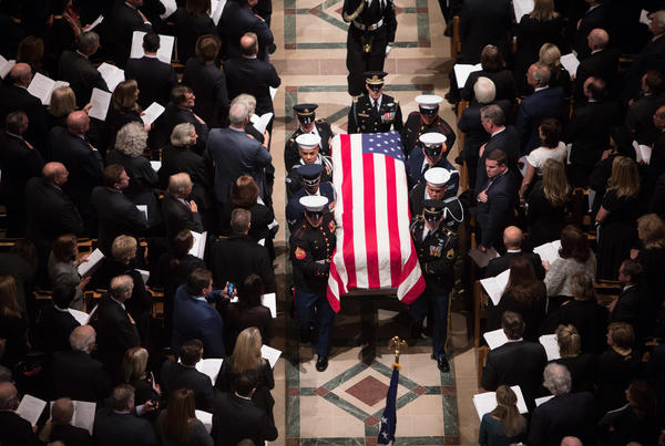 A joint military service honor guard carries the casket of former President George H.W. Bush at the end of his state funeral.