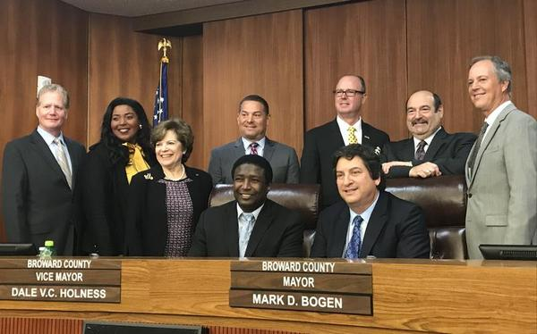 Broward County commissioners are divided over how much the county should force contracted companies to pay for their workers' health insurance.
