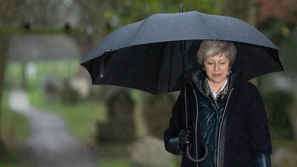 British Prime Minister Theresa May leaves a church service west of London in Sunday's pouring rain.