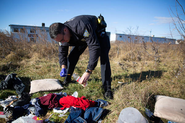 Officer Christian Bruckhart collects used needles from a vacant site in his patrol area in New Haven, Conn.